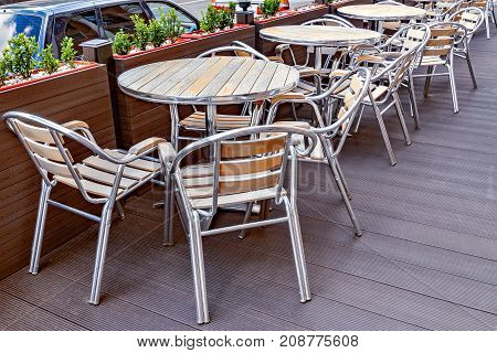 Chairs and tables on the territory of the street restaurant.
