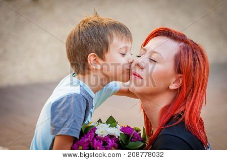 Little cute baby son kissing his mother. Mother's Day   stock image.
