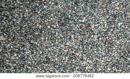 Stones on ground, background and texture form with a rocky surface on top. Gravel in the summer on the site.