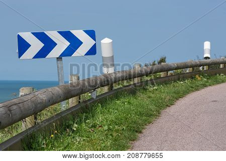 Country road with wooden crash barrier and traffic sign near coast of Normandy, France