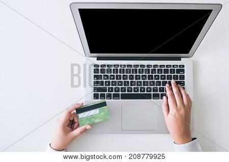 Business woman holding credit card entering security code and using laptop computer online shopping concept.