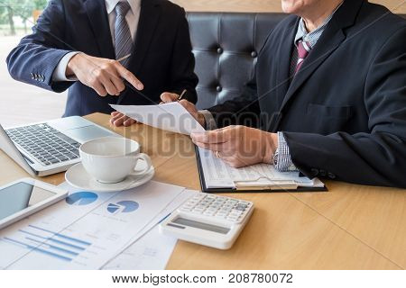 Two confident executives business colleagues meeting and discussing ideas of project about company offer they is pointing on a contract and giving explanations team of successful business people.