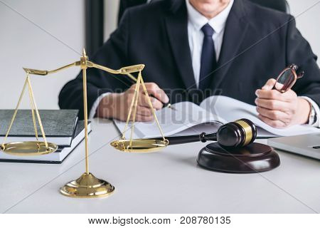 Close up of gavel Male lawyer or judge working with scales of justice Law book report the case on table in modern office Law and justice concept.