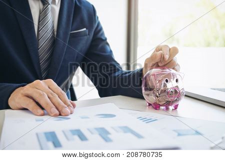 Businessman putting coins into piggy bank and using calculator to analysis business investment with many document graph data financial concept.