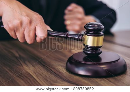 Male lawyer or judge hand's striking the gavel on sounding block working at courtroom Law and justice concept.