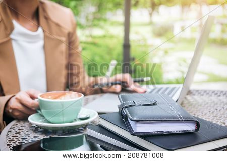 Work and relax Woman freelancer is working on computer laptop while sitting garden scenery background.