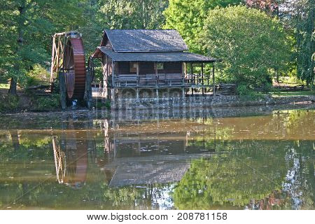 a restored gristmill, large metal waterwheel, reflected in a pond