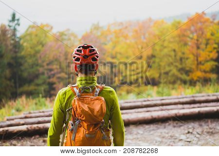 Mountain biker looking at inspiring mountain landscape standing with bicycle. Man cycling MTB on dirty road in woods. Sport and active recreation fitness motivation and inspiration.