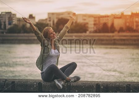 Happy woman enjoys sitting at the riverbank with her arms outstretched.
