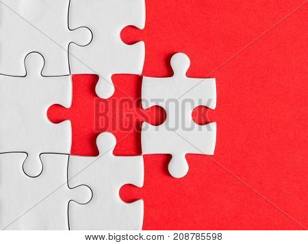 Closeup one white jigsaw puzzle beside missing jigsaw group on red background (Business Concept)