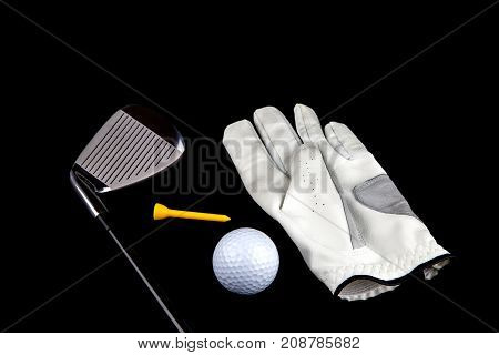 Golf club with glove ball and tee peg on a black background