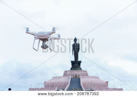 An unmanned aerial vehicle (UAV) or drone flying in the air with Phutthamonthon Isan background Thailand