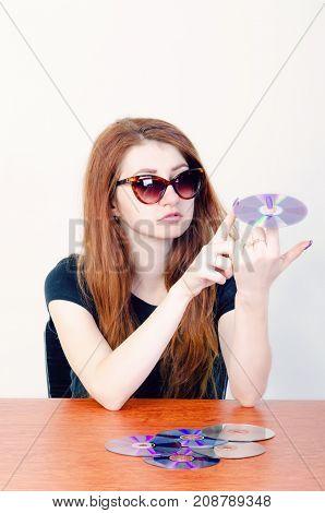 young girl holding a compact disc on her finger