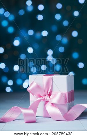 Gift box or present with pink bow ribbon against magic bokeh background. Greeting card for Christmas New Year or wedding.
