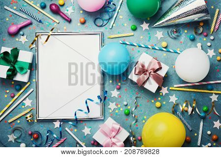 Party or birthday background. Silver frame with colorful balloon gift box carnival cap confetti candy and streamer on vintage blue table top view. Flat lay style. Holiday or festive mockup.