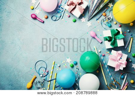 Funny birthday party background. Colorful balloon gift box confetti candy and streamer on turquoise table top view. Flat lay style. Copy space for greeting.