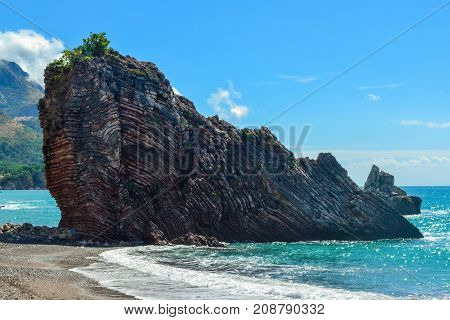 Beautiful sea view. The mountain goes into the sea. Calm sea on a sunny day. Adriatic Sea. Montenegro