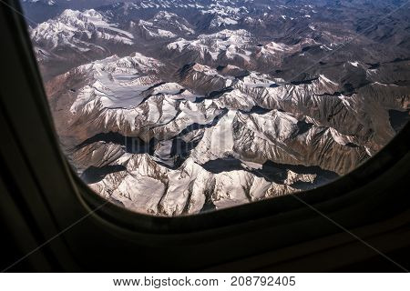 Top view image of the Himalaya mountain and blue sky horizon from airplane window