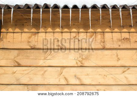 Icicles on the roof of a wooden house