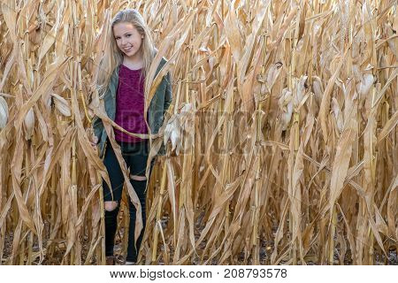 smiling young Caucasian girl in autumn cornfield