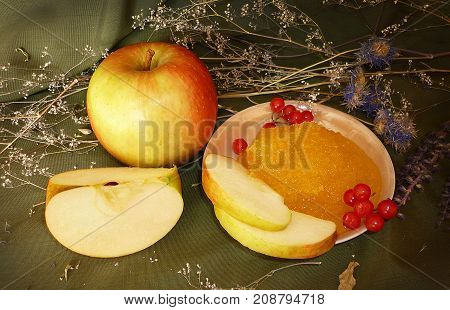 ripe apples with grapes in a basket on a green background