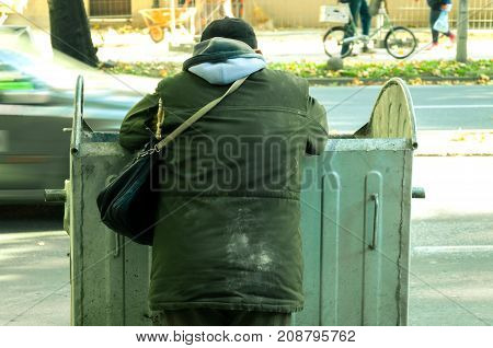 Poor and hungry homeless man in dirty clothes looking for food in the dumpster on the urban street in the city