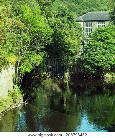 the river calder jpoining the smaller river in hebden bridge with trees houses and a heron in the water
