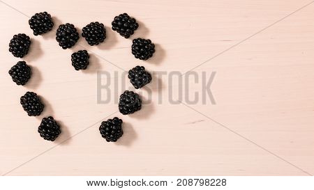 Fresh berries of blackberry fruits blackberries in form shape heart on wooden table background. Concept for healthy eating and nutrition. Top view