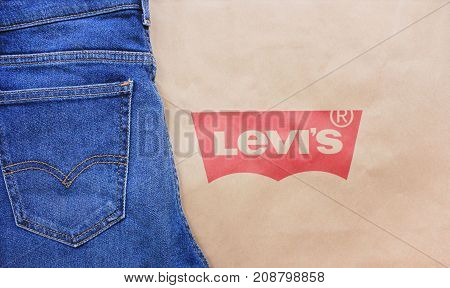 MOSCOW, RUSSIA - OCTOBER 8, 2017: Levi's Denim Blue Jeans with Company Logo on Paper Bag. Levi Strauss famous brand new basic style jeans isolated on brown textured background with empty copy space.