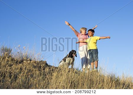 granny and grandson make a stretching on the evening hill. Spotted dog is near
