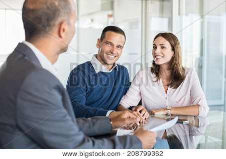 Mature financial advisor showing report to young couple for their investment. Salesman and positive couple talking about purchase. Happy couple consulting financial agent for loan.