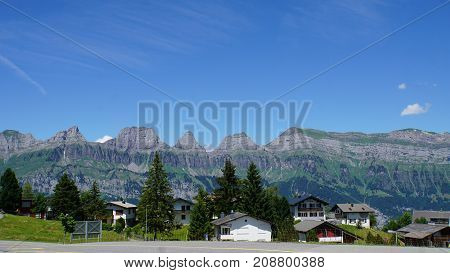 View from Flumserberg to the mountain chain of the Churfirsten in the canton of St. Gallen in Switzerland, in the foreground houses,