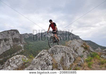 Young man riding a bike on rocks on the mountain, extreme riding bicycle off road on rocks