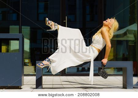 Elegant fashionable woman presenting trendy urban outfit. White crop top and trousers culottes. Outdoor photo session unusual bizarre pose
