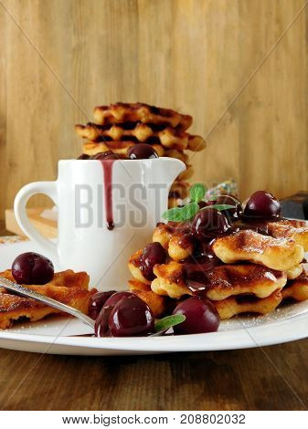 Waffles with cherry and chocolate sauce served on a white plate and in the white gravy boat