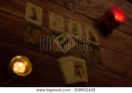 Soft focus mystic fortune telling playing cards fired candles background