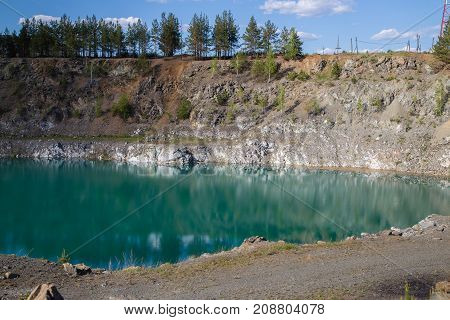 Abandoned flooded open pit quarry mine abestos ore with blue water