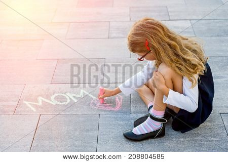 A little cute schoolgirl draws a colorful chalk on the sidewalk of LOVE MOM. After school outdoors