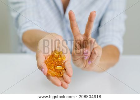Hands of a woman holding fish oil Omega-3 capsules and showing victory sign.
