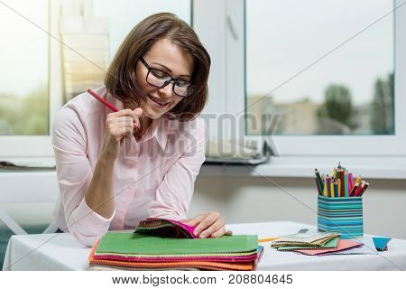 Interior designer at the workplace in the office with samples of fabrics and accessories for curtains and upholstery.