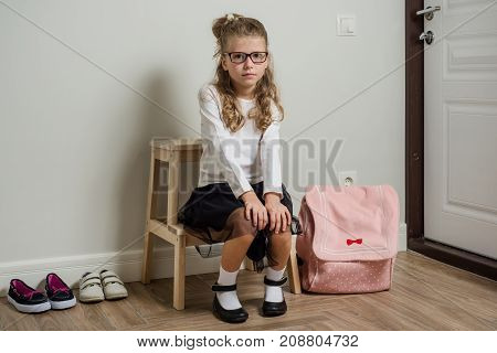 A pretty young schoolgirl with blond hair going to school sitting next to the door