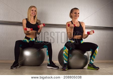 Two smiling women are sitting on pilates ball and doing biceps exercises with small weights on gray background.