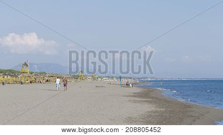 Ulcinsky Riviera - October 1 2017: Great beach on the Ulcinj Riviera people are resting and the blue Adriatic Sea and the mountains of Albania in the distance October 1 2017 Ulcinsky Riviera Montenegro