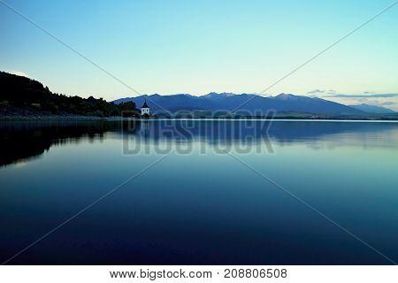 Mirroring on the water surface of Liptovska Mara at dusk. Water level, mirroring, blue sky and West tatras mountains. Beautiful Slovakia.