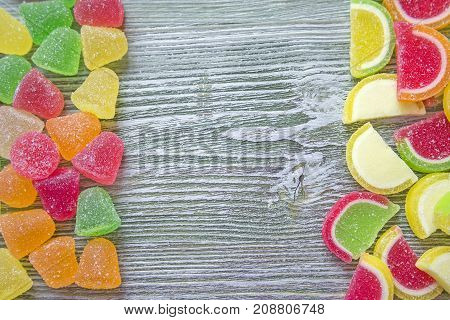 Sweet tasty sugary colorful marmalade vibrant candies or sweets top view. Wooden background with copy space
