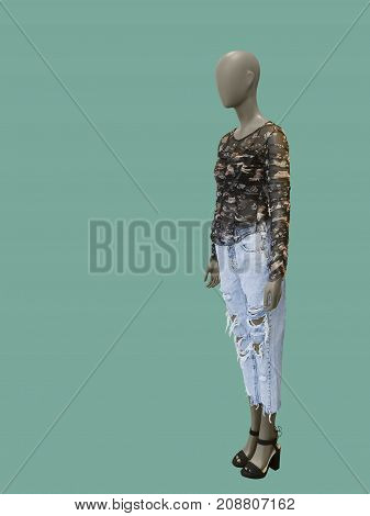 Full-length female mannequin dressed in blue jeans and blouse over green background. No brand names or copyright objects.