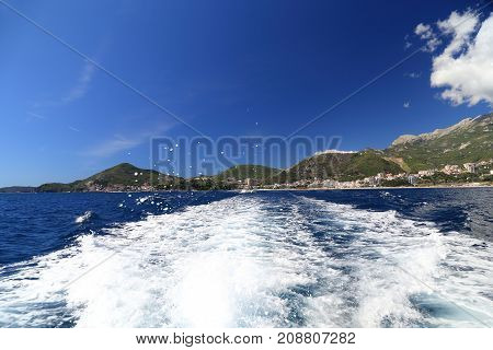 BECICI, MONTENEGRO - SEPTEMBER 14, 2013: It is a view of the settlement which remained behind the wake of the pleasure boat.