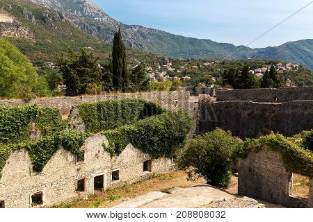 Old ruined medieval fortress called Spagnola in Herceg Novi Montenegro. Stone houses and walls covered by ivy and oleander. Neglected historical place. Mountains and town in the background.
