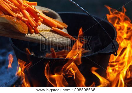 Tourist bowler with food on bonfire cooking in the hike outdoor activities. Preparation of pilaf or soup on fire.