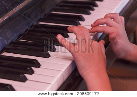 Child plays old piano his hands with fingers.